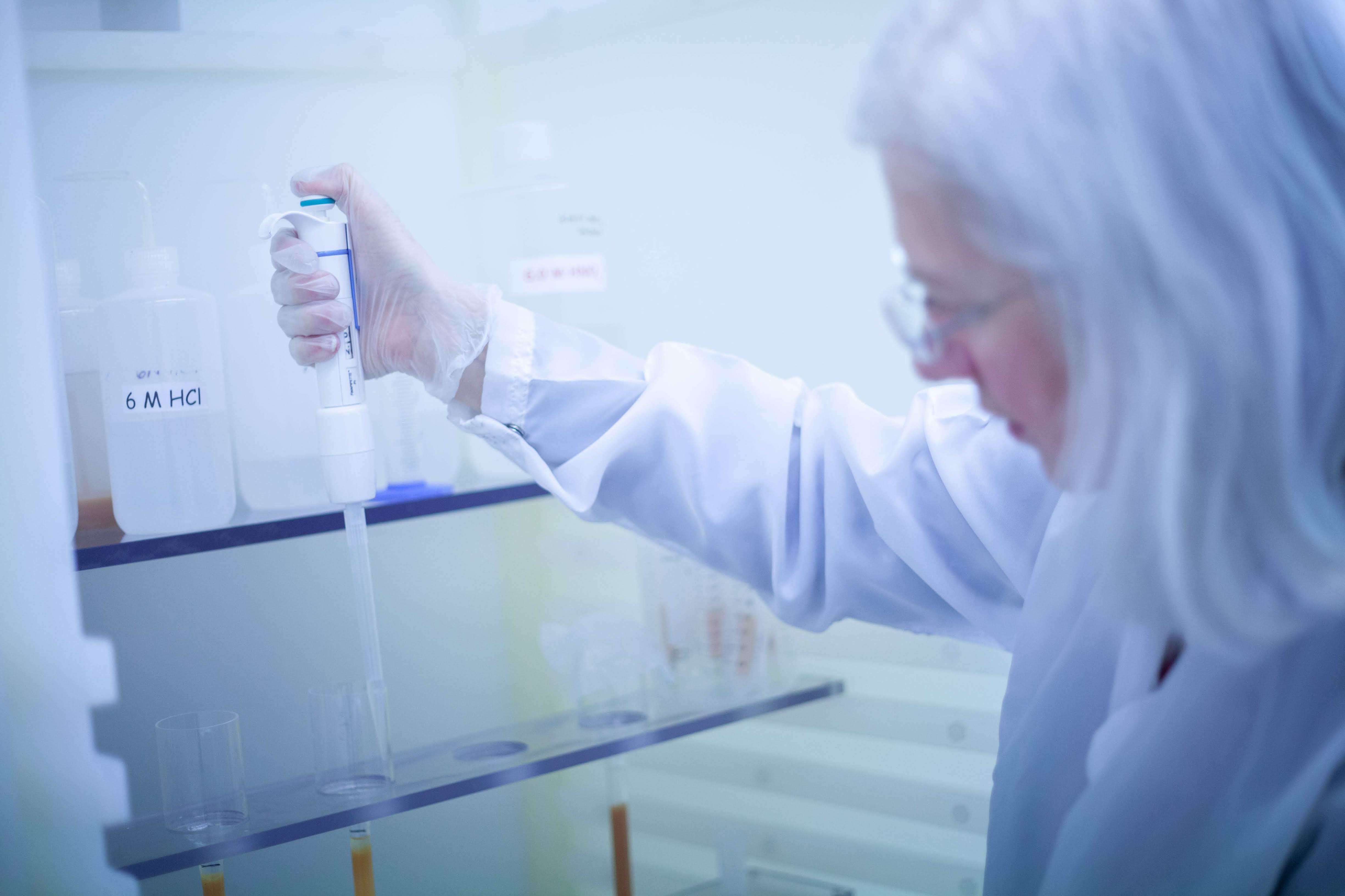 Mary Horan uses a pipette to run a liquid chromatography experiment.