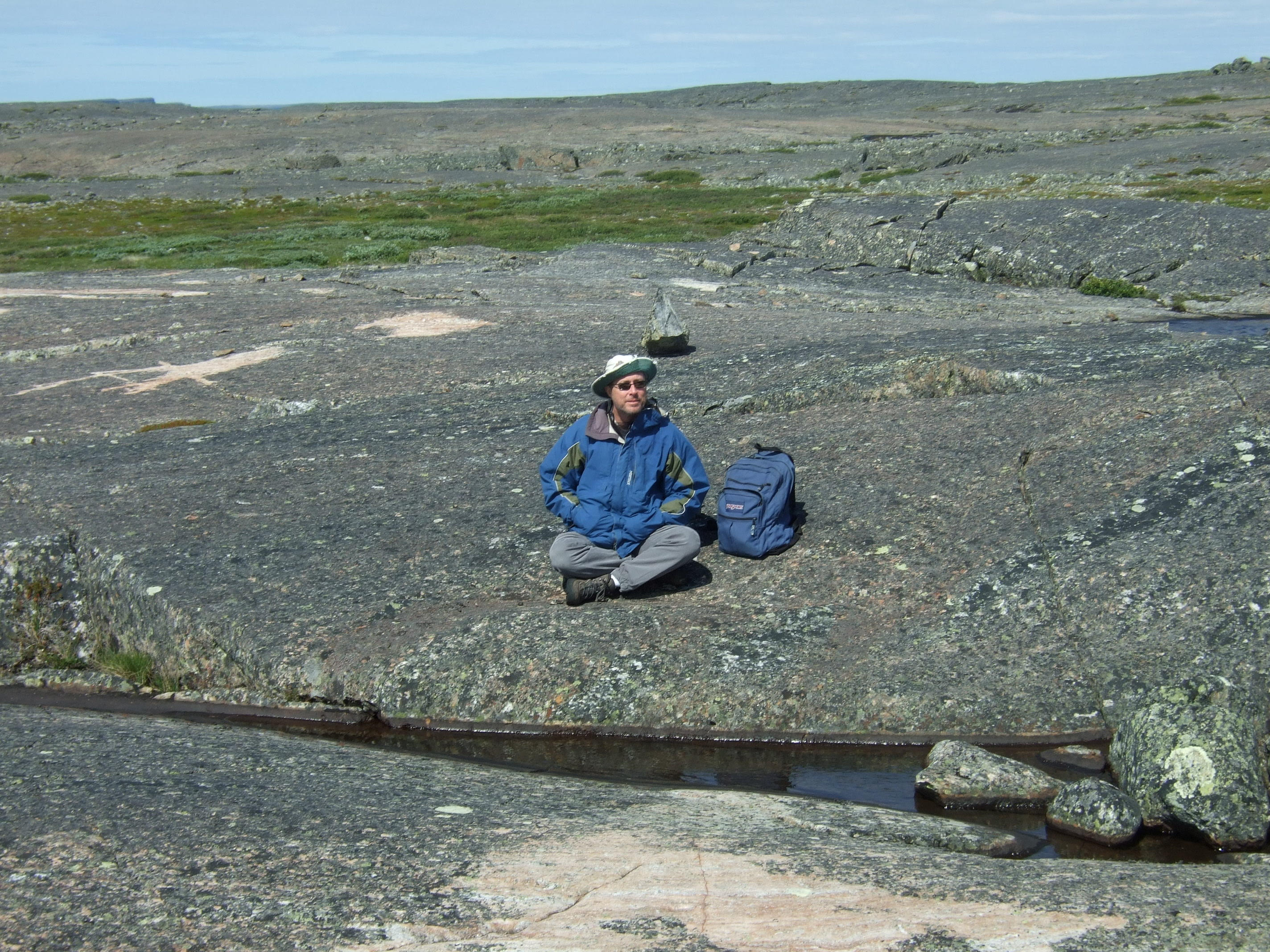 Rick Carlson sitting on 4.28 billion year old crust on the shores of Hudson's Bay.  Photo credit Jonathan O'Neil.