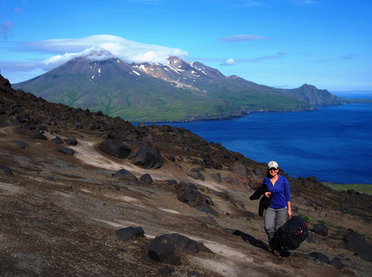 Carnegie's Diana Roman collecting samples from Alaska's Cleveland volcano, one of the most-active volcanoes in the Aleutians.  Tana Volcano on Chuginadak Island isn in the background. Photo is courtesy of Anna Barth of Lamont Doherty Earth Observatory
