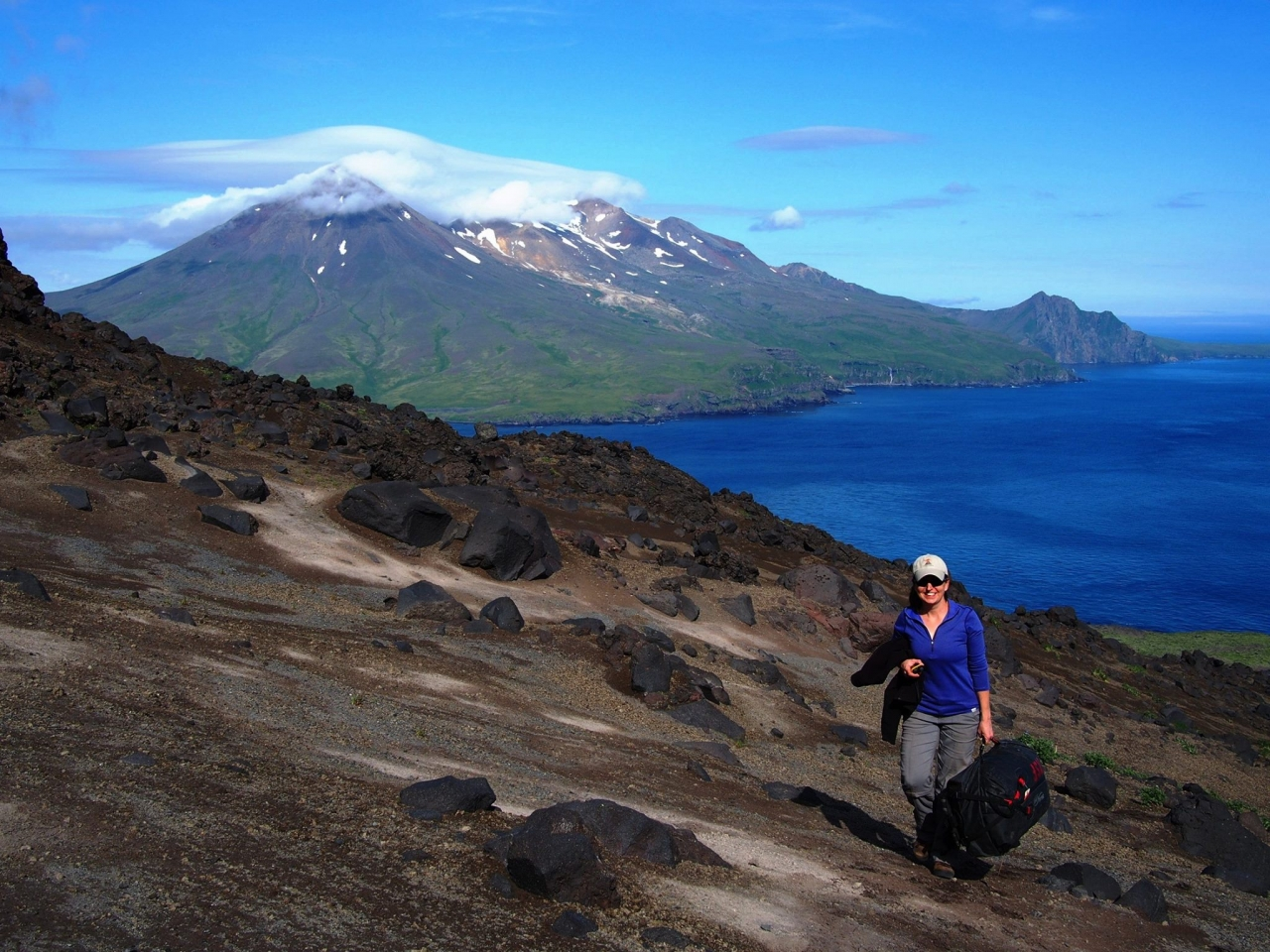 Carnegie's Diana Roman collecting samples from Alaska's Cleveland volcano, one of the most-active volcanoes in the Aleutians.  Tana Volcano on Chuginadak Island isn in the background. Photo is courtesy of Anna Barth of Lamont Doherty Earth Observatory.