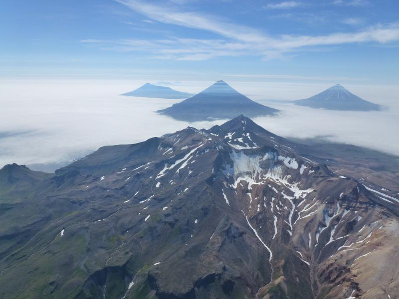 Aerial oblique photo of the volcanoes in the Islands of Four Mountains, Alaska. In the center is the summit of Mount Tana. Behind Tana are (left to right) Herbert, Cleveland, and Carlisle Volcanoes. USGS Photo by John Lyons, July 29, 2014.